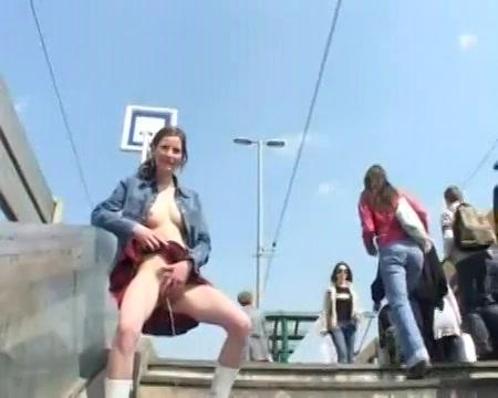 Halfnaakt meisje staat te plassen in het openbaar
