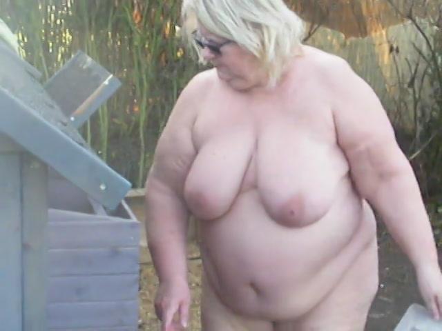 Dikke boerin voedert de kippen in haar nakie