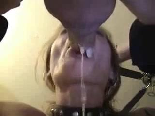 Hij houd haar hoofd vast wanneer hij diep in haar keel spuit