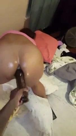 Een grote bruine dildo tussen haar negerinnenbillen