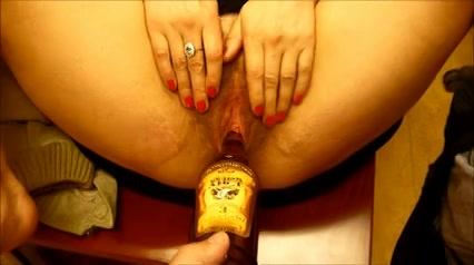 Een fles in haar harige dikke poes