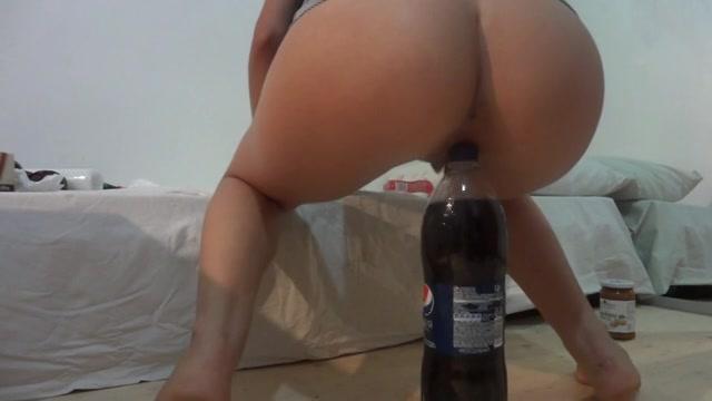 Voor de webcam laat ze haar kale kut over de grote cola fles zakken